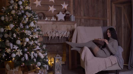 święta : A girl with long hair opens a box with a gift and rejoices sitting in a chair near the Christmas tree on Christmas day. 4K