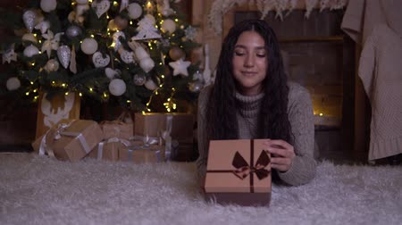 święta : The girl opens the box with a gift and rejoices lying on the floor near the Christmas tree Wideo