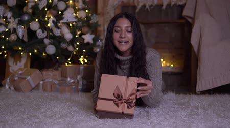 święta : The girl opens the box with a gift and rejoices lying on the floor near the Christmas tree. 4K