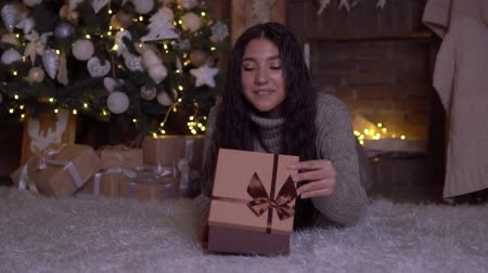 święta : The girl opens the box with a gift and rejoices lying on the floor near the Christmas tree.HD Wideo