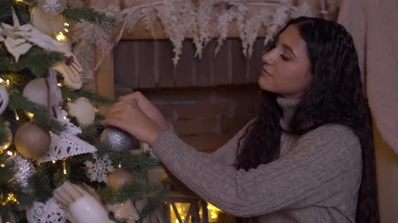 x mas : A young girl decorates a Christmas tree with a beautiful ball having a good mood.HD