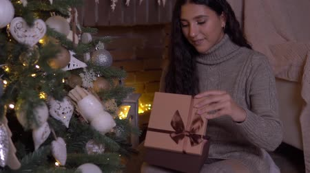 święta : The girl opens a gift on New Years Eve.HD