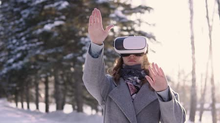 опыт : Attractive woman uses virtual reality glasses while having a good mood.