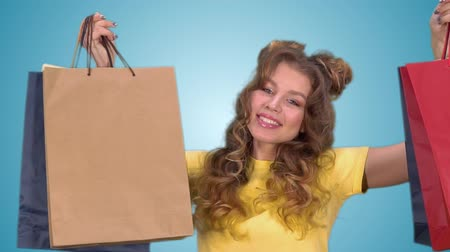 csodálkozás : Beautiful young girl holding multicolored shopping bags and smiling