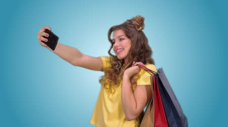 milan fashion : Happy beautiful girl makes selfie holding shopping bags