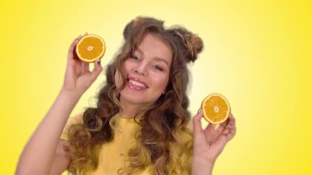 hides : attractive girl in a yellow shirt posing with oranges and smiling while looking at the camera