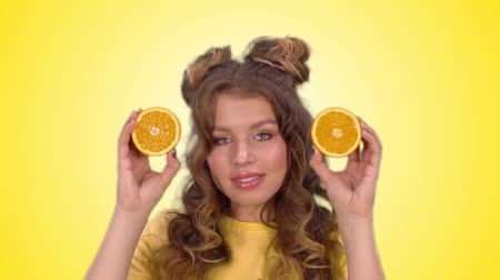 hides : attractive girl in a yellow vest closes her eyes with oranges and smiles looking into the camera Stock Footage