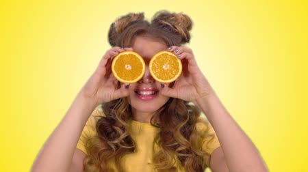 hides : Beautiful young girl in a yellow vest posing with oranges and smiling while looking into the camera. Stock Footage