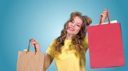 aprovado : beautiful young girl after shopping posing with packages and smiling looking into the camera Vídeos