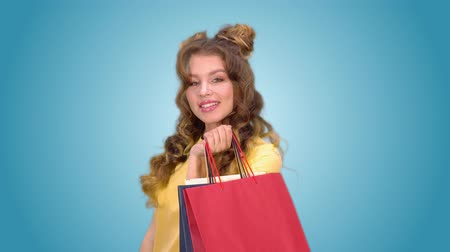 csodálkozás : beautiful young girl after shopping posing with packages spinning and smiling while looking into the camera
