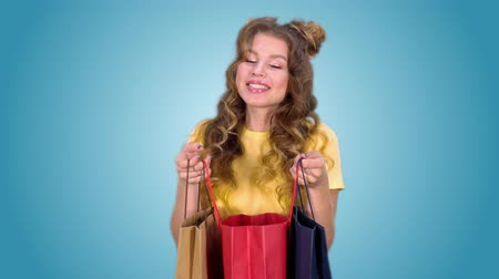 承認された : a beautiful young girl in a yellow t-shirt after shopping opens the package and enjoys shopping