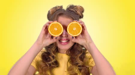 hides : beautiful young girl with laying posing with oranges and smiling looking into the camera on a yellow background Stock Footage