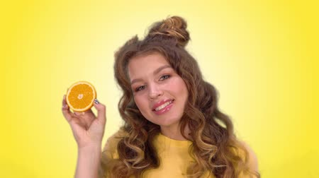 hides : beautiful young girl with styling poses with an orange winks and smiles while looking into the camera