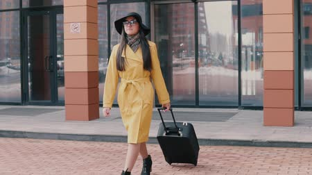 proceed : stylish girl with long hair in a hat and glasses comes with luggage