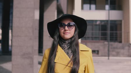 proceed : stylish girl with a good mood in a yellow raincoat hat and glasses comes with luggage