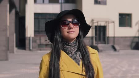 chegada : beautiful girl in a yellow raincoat hat and glasses comes with luggage
