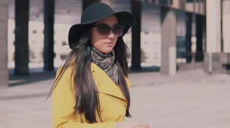 bijouterie : stylish girl in a yellow coat with long dark hair in a hat walks down the street takes off his glasses and looks around