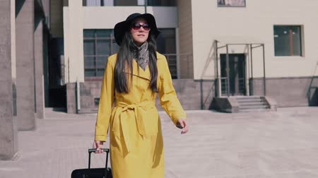 pace : stylish girl in a yellow raincoat hat and glasses with luggage rush and catches a taxi