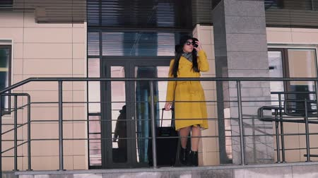 proceed : beautiful woman with long dark hair in a yellow raincoat and a hat goes out on the porch of the hotel takes off her glasses and looks around
