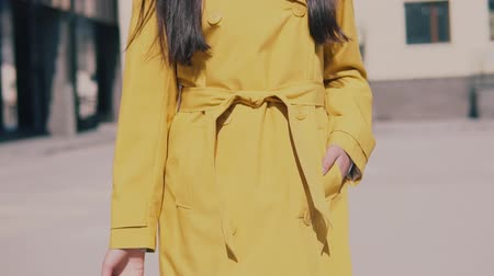 bagagem : beautiful woman in a yellow raincoat hat and glasses walks down the street with luggage and smiling