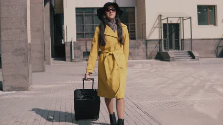 pace : stylish young girl in a yellow raincoat hat and glasses comes with luggage Stock Footage