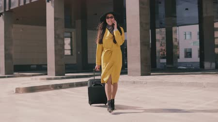pace : stylish girl in a yellow raincoat hat and glasses goes with luggage and talking on the phone and laughs Stock Footage