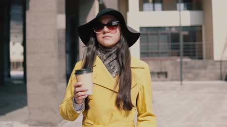 навынос : stylish young girl in a yellow raincoat hat and glasses walks down the street looking around and drinking coffee