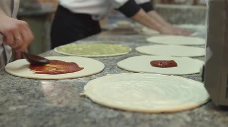 chefs table : A group of  chief evenly put the sauce on the circles of the dough for making pizza