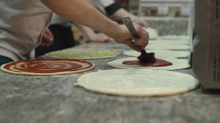 yum yum : A group of  chief in uniform uniformly put tomato sauce on pizza dough circles.