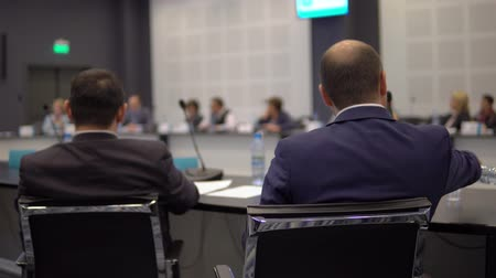 collegezaal : businessman pours and drinks water at a round table at an economic forum in a conference room Stockvideo