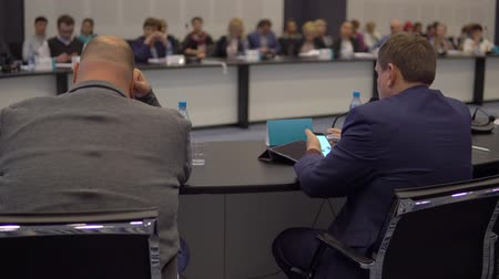 collegezaal : Businessman uses a smartphone while sitting at a round table in a conference room at an economic forum