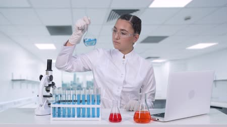 фельдшер : A female researcher analyzes the liquid in the flask and does clinical trials. Female scientist conducts genetic research and writes the results to a laptop