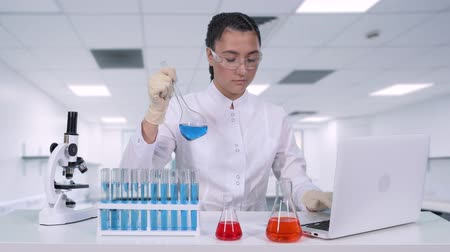 фельдшер : A female researcher analyzes the liquid in the flask and does clinical trials. A female scientist conducts genetic research and writes the results to a laptop in an innovation laboratory Стоковые видеозаписи