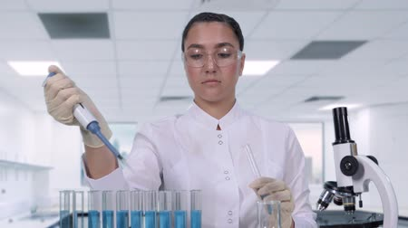 pipette : A female scientist examines a blue liquid using a micropipette and test tube. A female researcher is conducting clinical trials. science lab Stock Footage