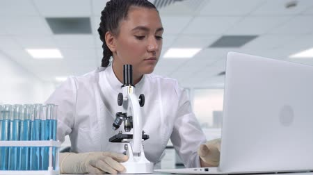 clínico : A female researcher looks at biological samples under a microscope, conducts clinical trials and writes data to a laptop while sitting at a white table. Scientific laboratory