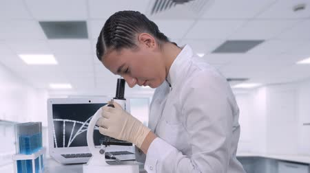 bakıyor : A female lab technician sitting at a table next to a laptop in a chemical laboratory looks at biological samples under a microscope. Conducts a study of dna molecules