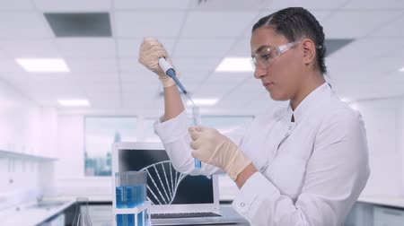 pipette : A female lab technician transfers a blue liquid sample to a test tube using a micropipette while sitting at a table in a science lab.