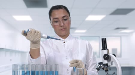 Образцы : A female scientist examines a blue fluid sample using a micropipette and test tubes while sitting at a table in the newest medical laboratory. Slow motion