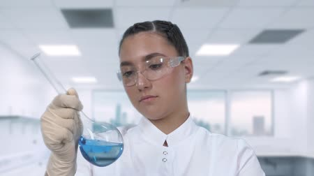 banka : A female lab technician examines a blue liquid in a glass flask and conducts clinical research in a science lab. Close-up plan.slow motion