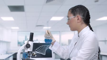 tudós : A female lab technician is researching a cure for cancer. A female scientist is conducting clinical trials. A scientific discovery in the field of medicine.slow motion