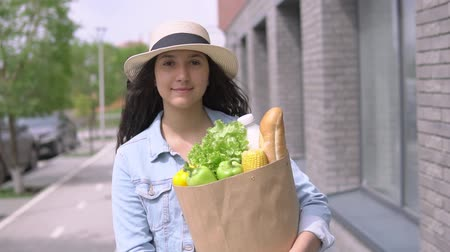 cash free : Young beautiful woman in a denim jacket and hat carries a package with products having a good mood and smiles.