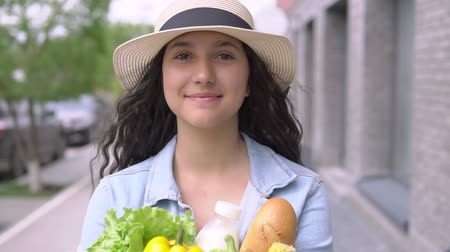 dietético : A young attractive woman in a denim jacket and hat carries a grocery bag while having a good mood and is smiling. Close-up