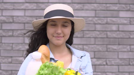 nutricional : A young beautiful girl in a denim jacket and hat is holding a bag of vegetables, milk and bread in a good mood and smiling while looking into the camera.