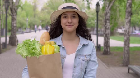 バゲット : A young beautiful woman in good mood walks down the street in a city park and carries a large grocery bag. 動画素材