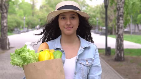 jó hangulatban : Young beautiful woman carries a bag with products in a good mood. Slow motion