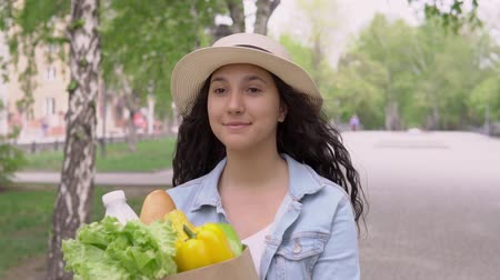 dietético : Young beautiful woman in a denim jacket and a good mood hat carries a bag of groceries and smiles.slow motion Stock Footage