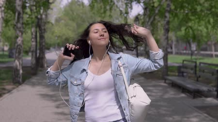 taniec : funny girl with long hair walks down the street and dances listening to music on headphones