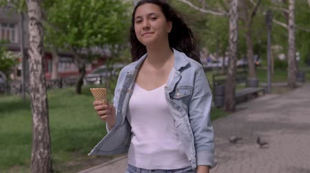 vacations cones : A beautiful young girl walks down the street and eats ice cream on a hot summer day while having a good mood.