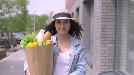 груша : Young beautiful woman in a denim jacket and hat carries a package with products having a good mood and smiles. 4K