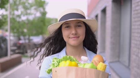 cash free : A young attractive woman in a denim jacket and hat carries a grocery bag while having a good mood and is smiling. Close-up. 4K